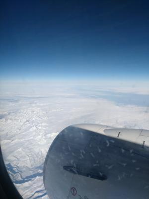 Flug über die schneebedeckten Alpen in Richtung Zuhause