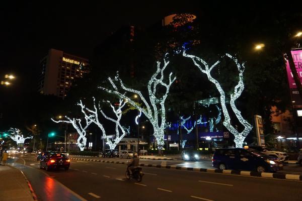 Neben den prächtig beleuchteten Bäumen, die vor allem in den Stadtteilen KLCC und Bukit Bintang zu finden sind, ist hier auch der in Malaysia geltende Linksverkehr zu sehen.