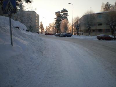 [Bild: schneebedeckte Straße im Wohngebiet]